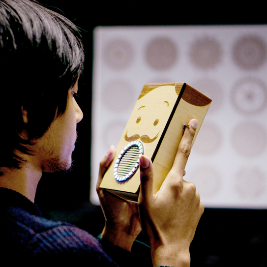 A person interacting with a cardboard talking device